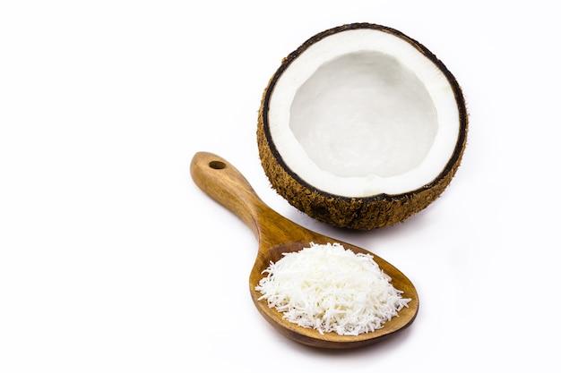 Houten lepel met geraspte kokos en kokos op de achtergrond, geïsoleerd op een witte achtergrond met kopieerruimte, culinair ingrediënt