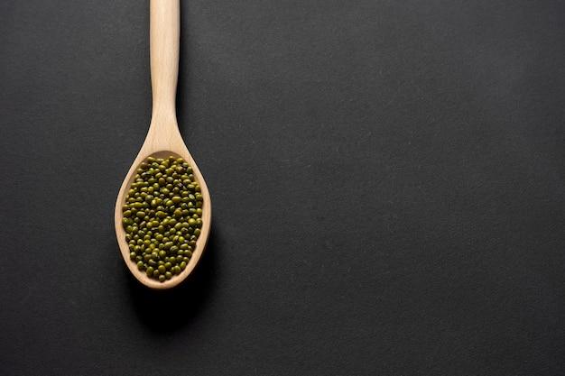 Houten lepel met groene bonen op een zwarte achtergrond. copyspace.