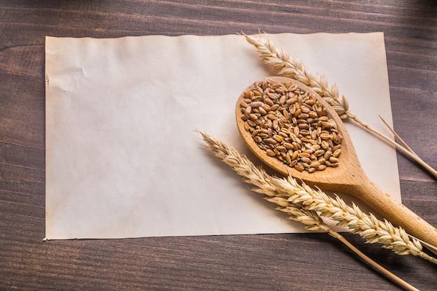 Houten lepel met munten van tarwe en oren op oud papier vintage houten bord