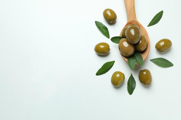 Houten lepel met olijven op witte achtergrond, ruimte voor tekst