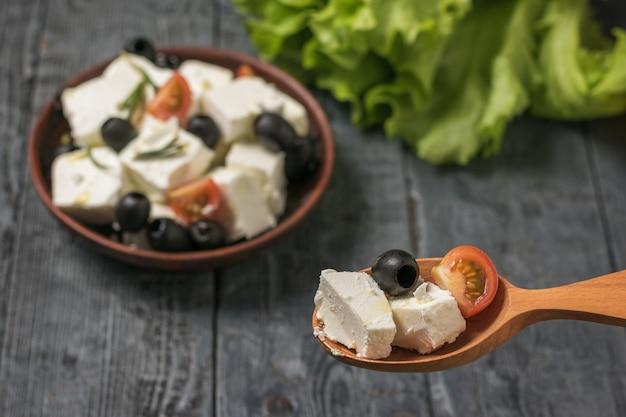 Houten lepel met plakjes kaas en tomaten op de achtergrond van een bord met salade. salade met kaas en groenten.
