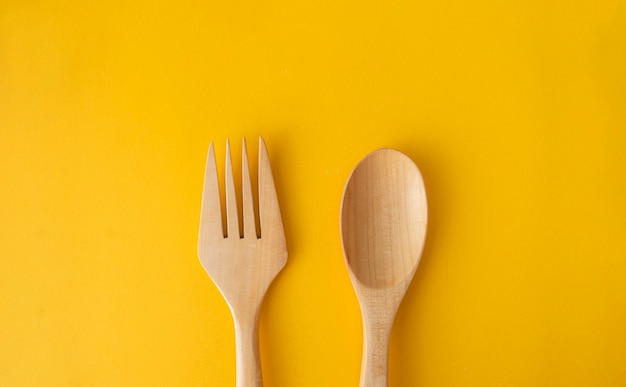 Houten lepel op gele ruimte in voedsel ruimteconcept