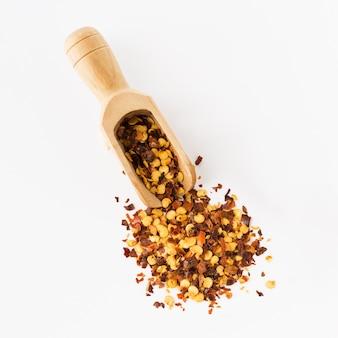 Houten lepel vol gemalen rode cayennepeper, gedroogde chili vlokken en zaden geïsoleerd op een witte