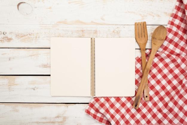 Houten lepels en andere kokende hulpmiddelen met rode servetten op de keukenlijst.