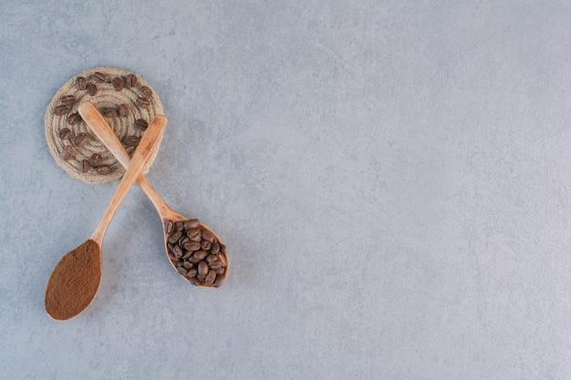 Houten lepels gemalen en gebrande koffiebonen op stenen tafel.