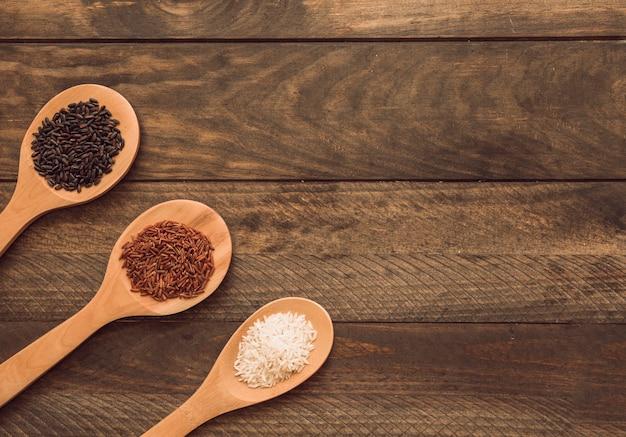 Houten lepels met drie verschillende soorten rijstkorrels op houten plank