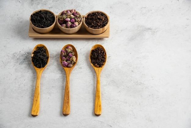 Houten lepels met gedroogde rozen, losse thee en kruidnagel.