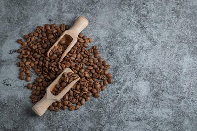 Houten lepels met koffiebonen op een grijze achtergrond.