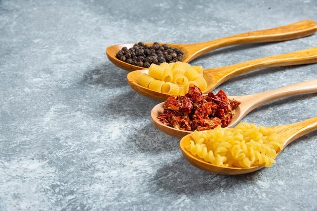 Houten lepels rauwe pasta op marmeren achtergrond.