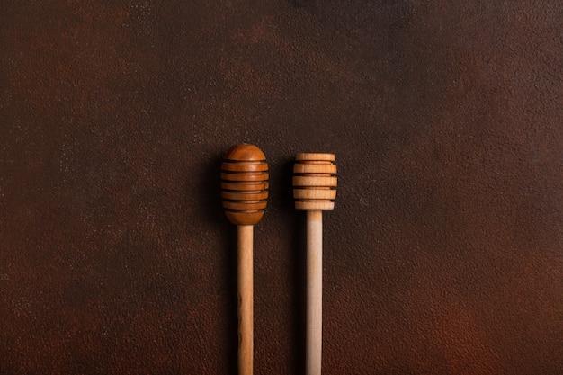 Houten lepels voor honing op een donkere tafel