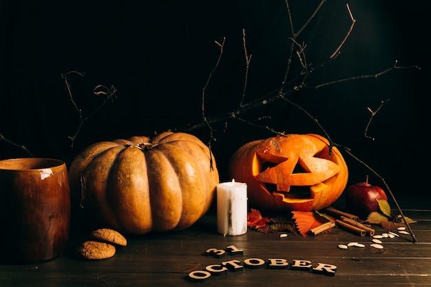 Houten letters '31 oktober 'liggen voor grote hallooween pompoenen