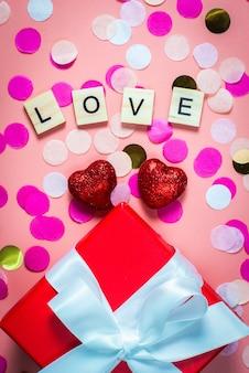 Houten letters bekleed met liefde, grappige felicitaties op een roze tafel. plat lag, bovenaanzicht. rode glanzende harten.
