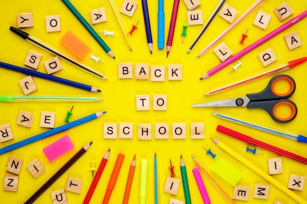 Houten letters gerangschikt in zin terug naar school en kantoorbenodigdheden op geel