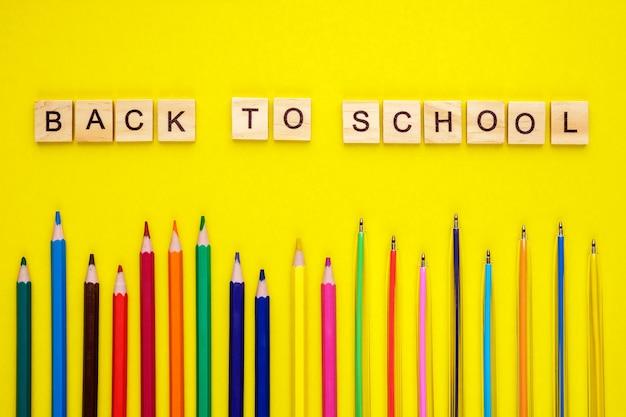 Houten letters gerangschikt in zin terug naar school, potloden en pennen op geel