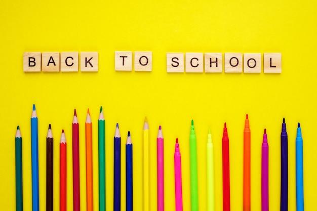 Houten letters gerangschikt in zin terug naar school, potloden en viltstiften op geel