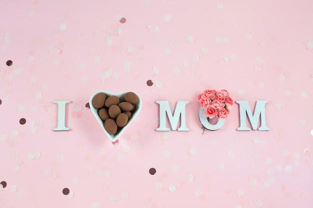 Houten letters in de zin i love mom met bloemen en chocoladesuikergoed op een roze bureau.