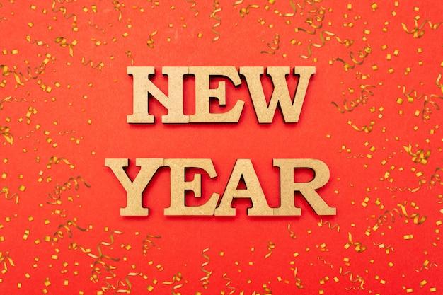 Houten letters in een new year's cap op een rode achtergrond met snoep.