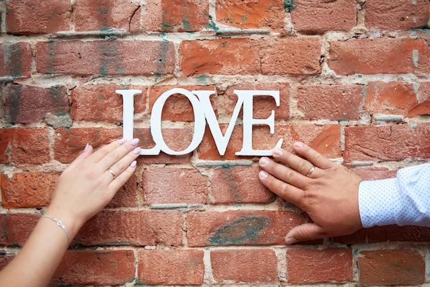 Houten letters liefde voor valentijnsdag en vrolijk kerstfeest op een rode bakstenen muur vastgehouden door mannelijke en vrouwelijke hand met trouwringen.
