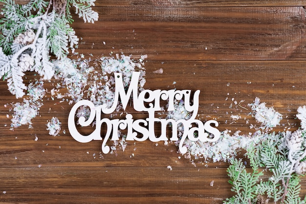 Houten letters merry christmas met fit takken en sneeuw op een houten achtergrond. kerstkaart. plat leggen
