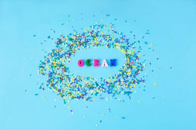 Houten letters met woord ocean rond kleine plastic deeltjes op een blauwe achtergrond.