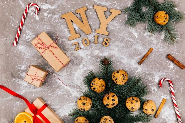 Houten letters 'ny 2018' liggen in de vloer omringd door koekjes, dennentakken, roodwit snoepjes en huidige dozen