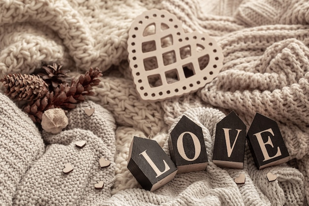 Houten letters vormen het woord liefde op een achtergrond van gezellige gebreide artikelen.