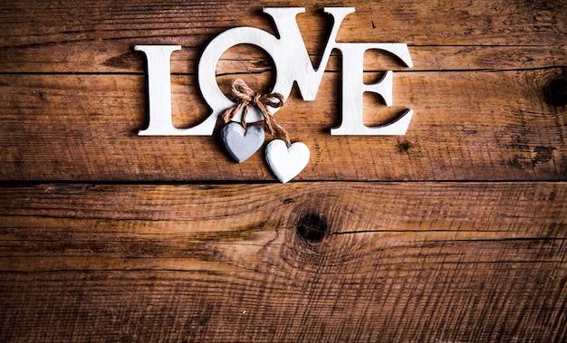 Houten letters vormen woord liefde geschreven op houten achtergrond. valentijnsdag. twee harten