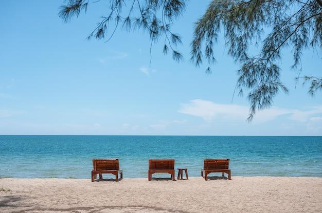 Houten ligstoel op het strand met boom bedekt met tropische zee op zonnige dag