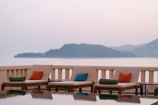 Houten ligstoelen bij het zwembad bij de villa aan zee, bij zonsondergang
