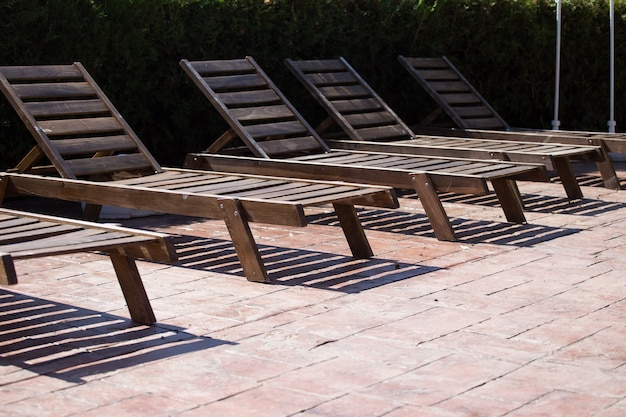 Houten ligstoelen bij het zwembad. zonder mensen.