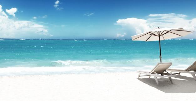 Houten ligstoelen op zandstrand in de buurt van zee. vakantie achtergrond.
