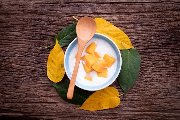 Houten lijst met voedingsyoghurt met bovenste laagje gesneden mango's.