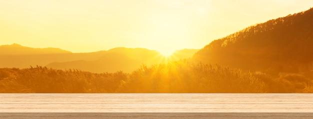 Houten lijstbovenkant en onduidelijk beeldzonsopgang of zonsondergangachtergrond voor product