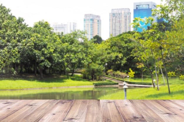 Houten lijstbovenkant over onscherp groen park op de stadsachtergrond.
