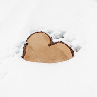 Houten log bedekt met sneeuw