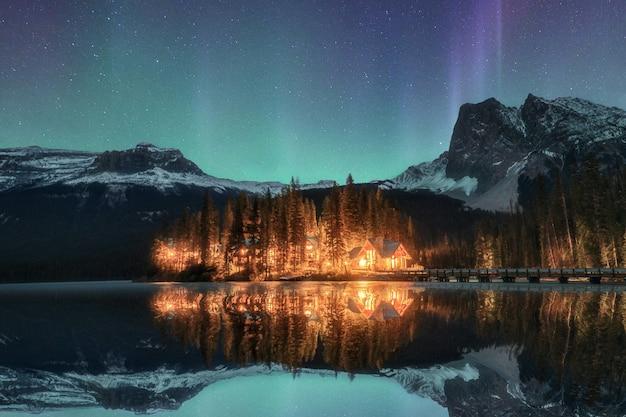 Houten loge verlicht met aurora borealis op emerald lake in yoho national park
