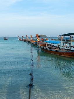 Houten longtailboten die op blauwe zee met ankertouw op lipe island, satun, thailand, vreedzaam uitzicht op zee, schilderachtige, reis- en ontspanningsplaats, traditioneel vervoer