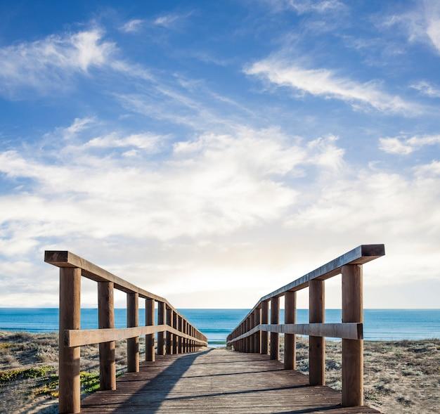 Houten loopbrug over het zand