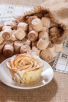 Houten lottovaten in zakje en speelkaarten voor een spel in lotto met zelfgemaakt koekje in de vorm van roos op witte schotel