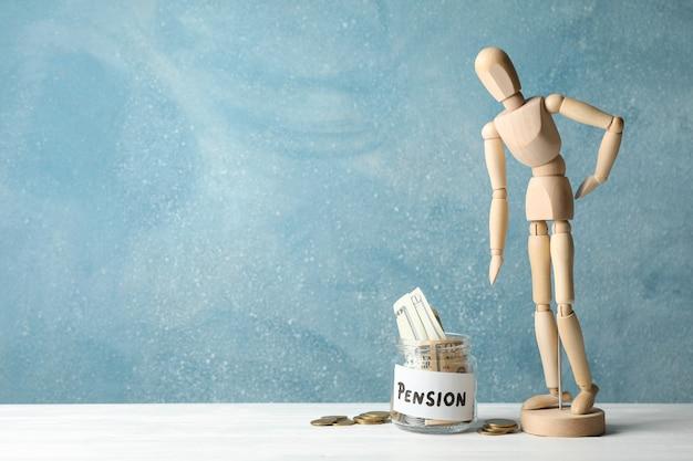 Houten man en pot met geld tegen blauw, ruimte voor tekst