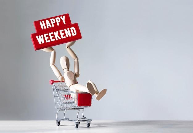 Houten man houdt een rood houten blok met woord happy weekend, concept.