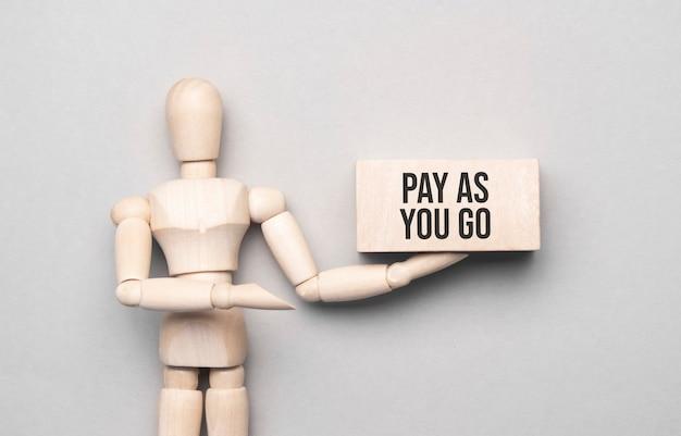 Houten man toont met een hand aan een wit bord met de tekst pay as you go