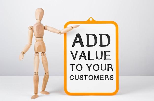 Houten man toont met een hand op wit bord met tekst voeg waarde toe aan uw klanten.