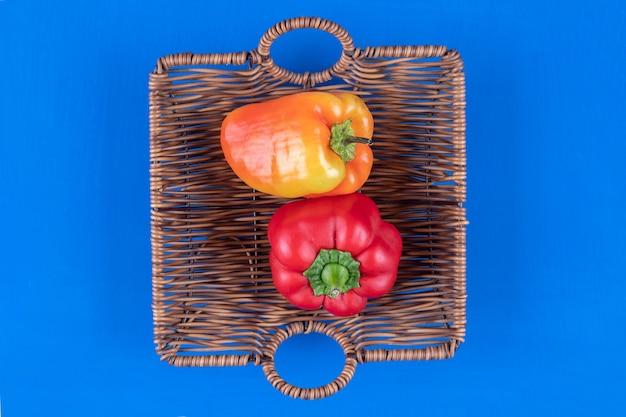 Houten mand met kleurrijke paprika's op blauwe tafel.