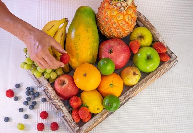 Houten mand vol met vers fruit op een witte achtergrond. citrusvruchten, papaya, ananas, banaan, peer, appel, aardbei, granaatappel, bosbes. vrouwelijke hand met een aardbei