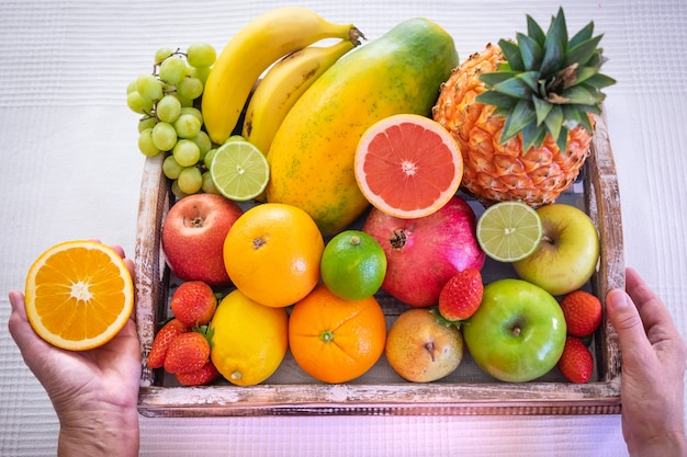 Houten mand vol met vers fruit op een witte achtergrond. citrusvruchten, papaya, ananas, banaan, peer, appel, aardbei, granaatappel, bosbes. vrouwelijke hand met een halve sinaasappel