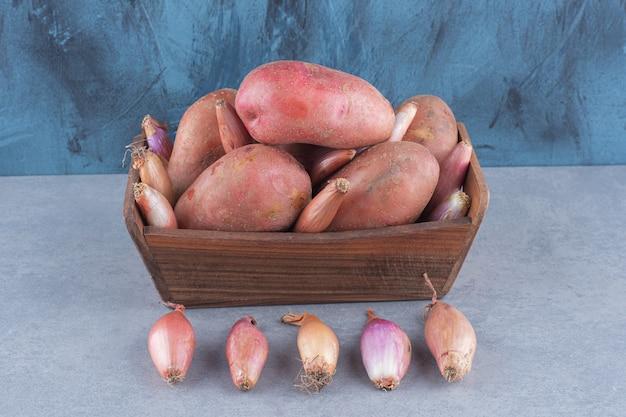 Houten mand vol rode aardappel en ui.