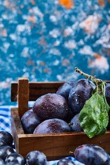 Houten mandje met verse pruimen op blauw.
