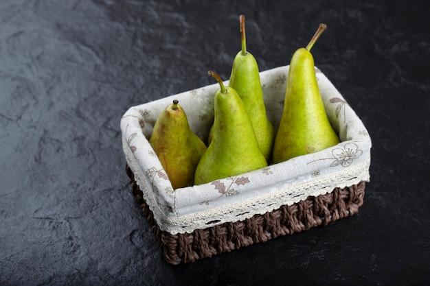 Houten mandje van rijpe groene peren op zwarte achtergrond.