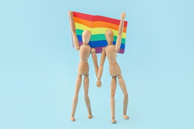 Houten mannequins en regenboogvlag op blauw